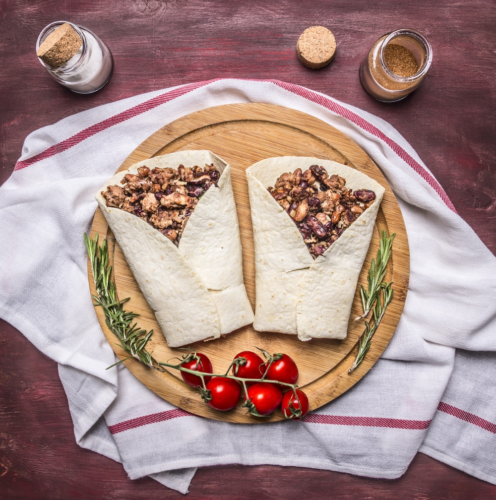 burrito with meat and vegetables on a cutting board with tomatoes and garlic  on a napkin on wooden rustic background top view